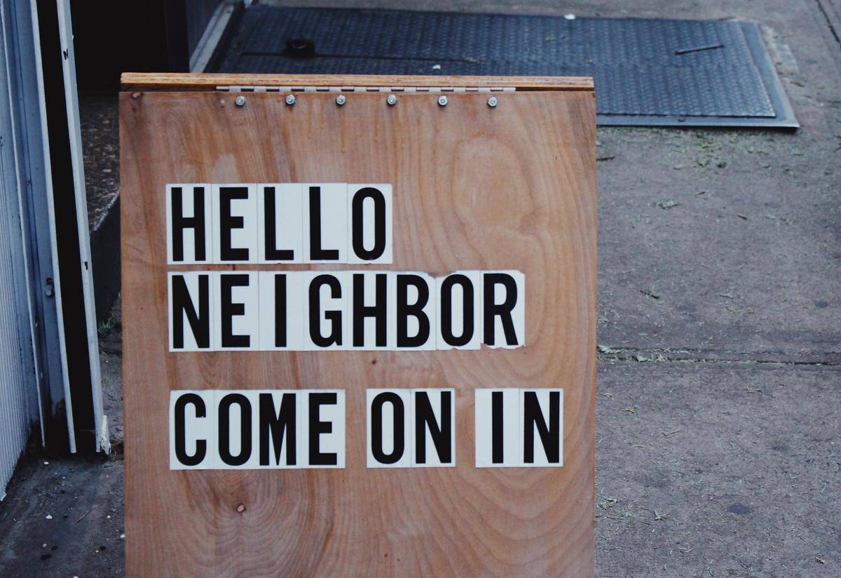 a wood sign that reads Hello neighbor come on in