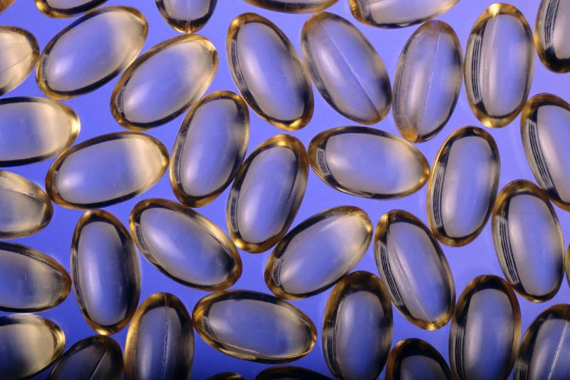 Omega-3 supplement capsules sit against a blue background.