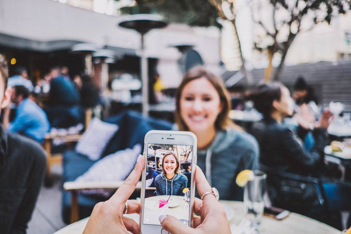 a girl getting her photo taken at an outdoor restaurant