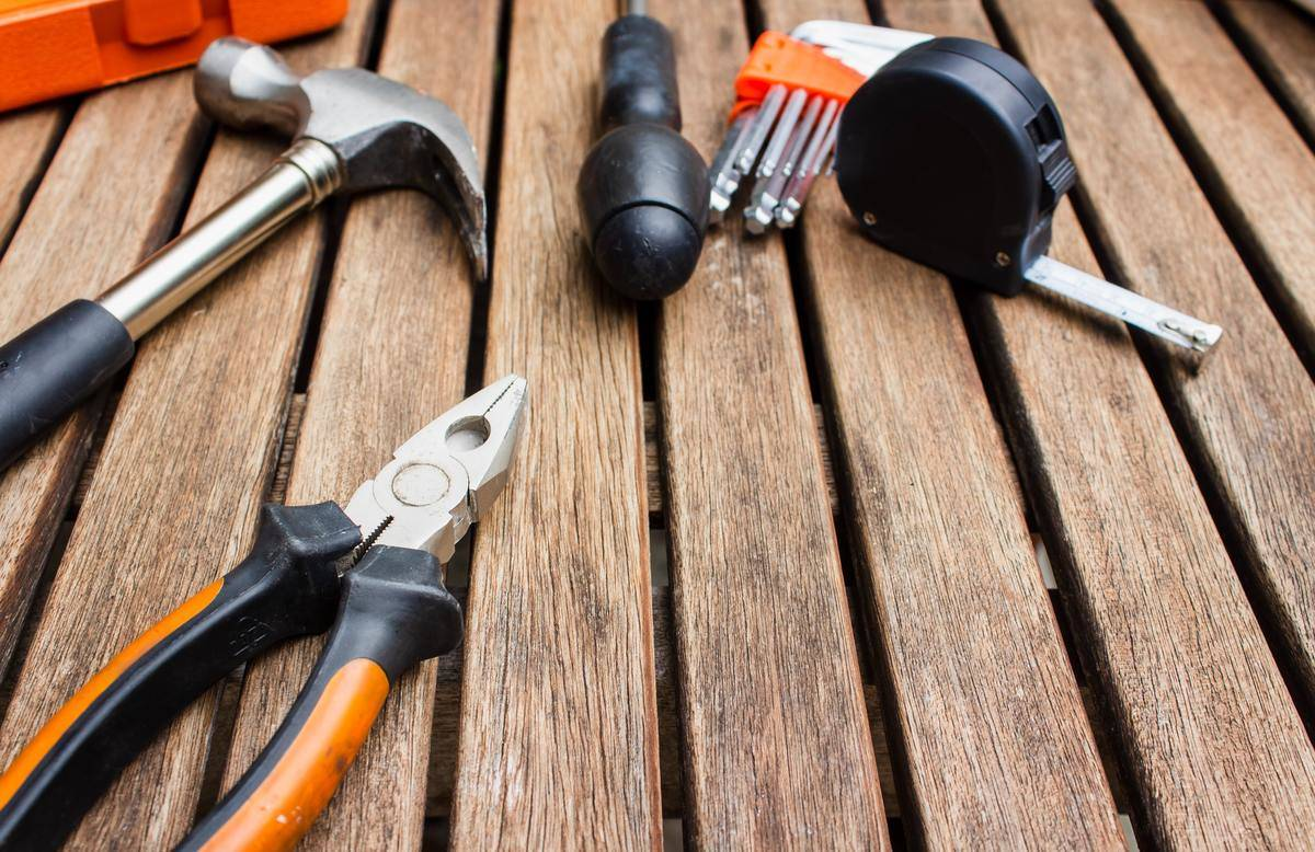a hammer, plyers, tape measure, and other tools on a wood surface