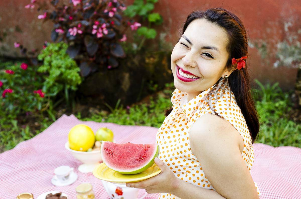 A woman winks and holds a plate of watermelon.