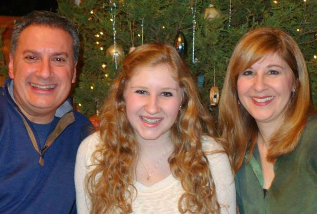 Rebecca and her parents, Joe and Jennifer, are in front of their Christmas tree.