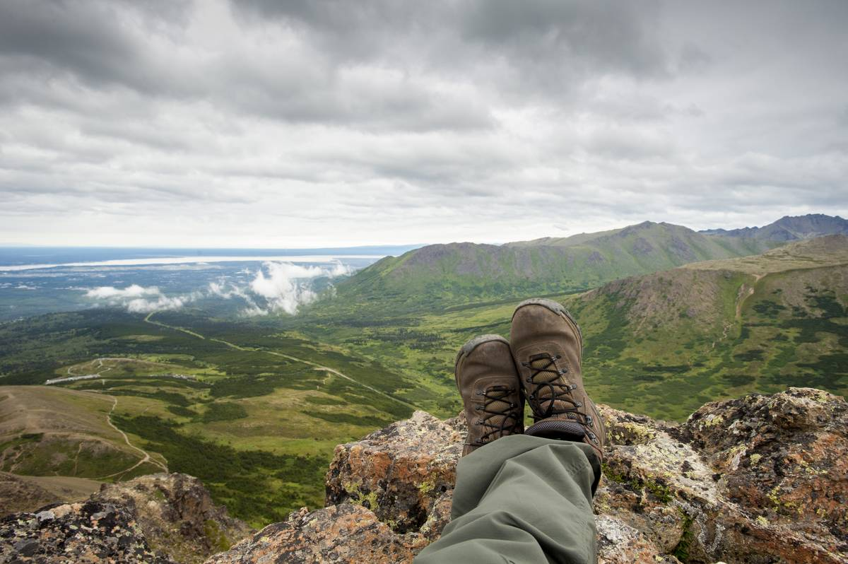 A hiker sits down, looking out at the Chugach Mountains near Anchorage, AK.