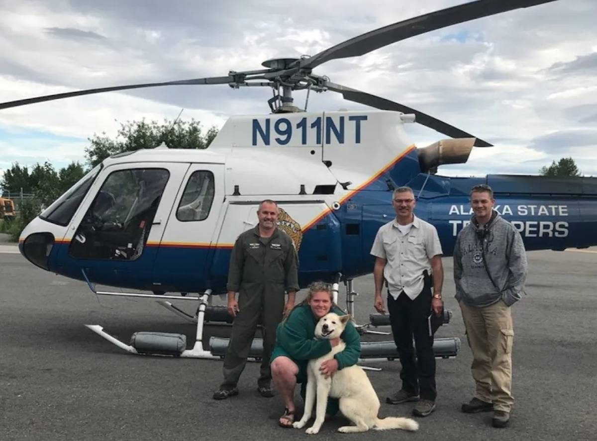 Milling, Nanook, and the Alaskan State Troopers take a photo in front of the helicopter that rescued Milling.