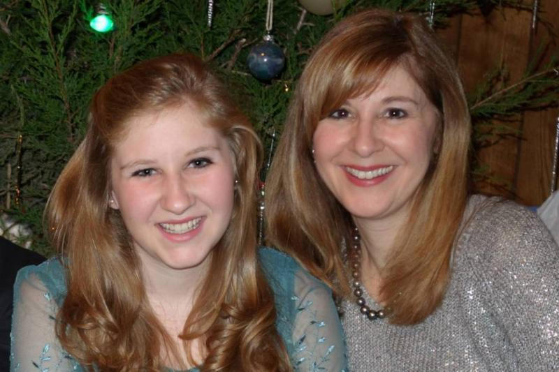 Rebecca takes a photo with her mother in front of a Christmas tree.