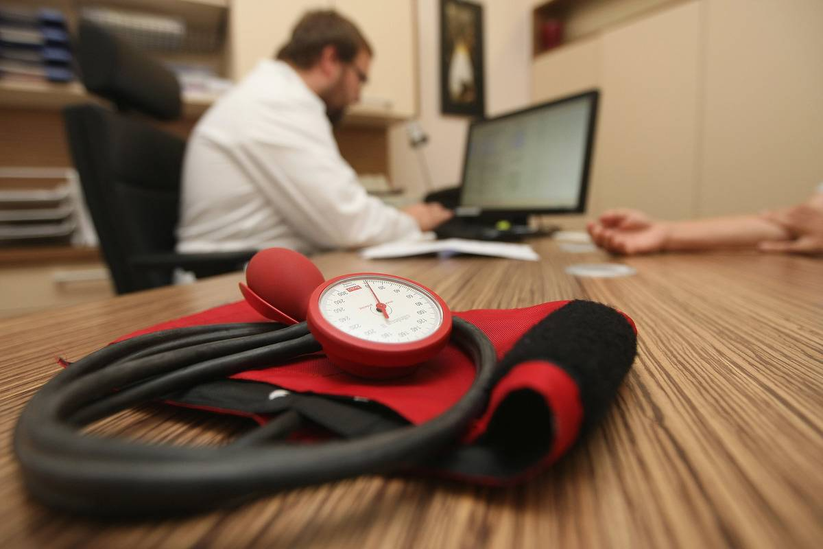 A sphygmomanometer, or blood pressure meter, is seen on a doctor's desk in his office.