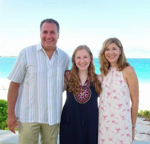All three members of the Cartellone family are photographed in front of the beach.