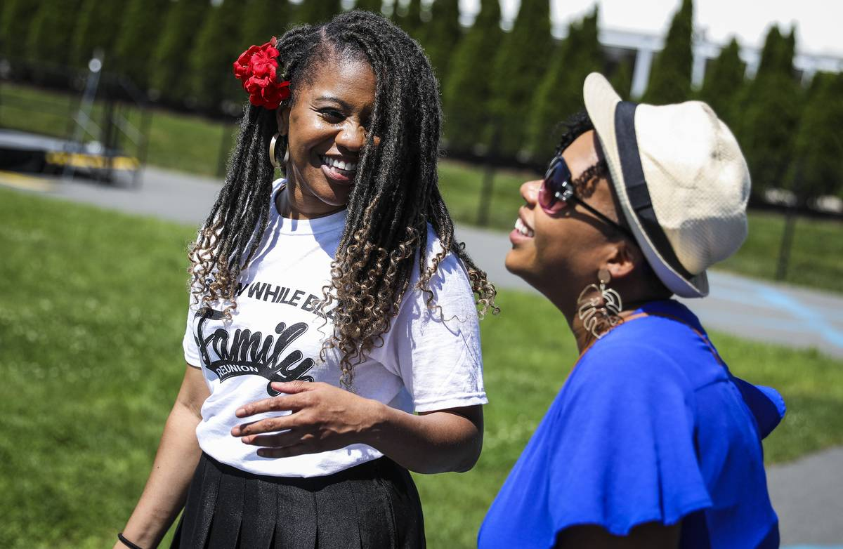 Two women talk and laugh with each other.