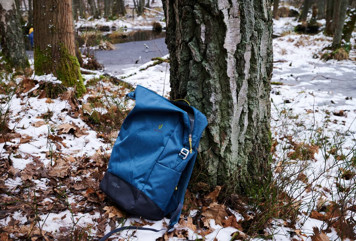 A hiker leaves their backpack against a tree.