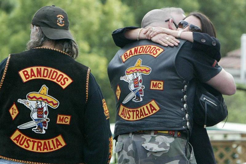 bandidos hugging a woman at a funeral