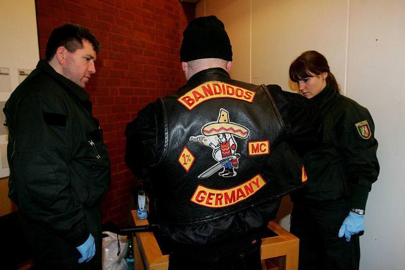 Policemen surround a member of the biker group 'Bandidos'