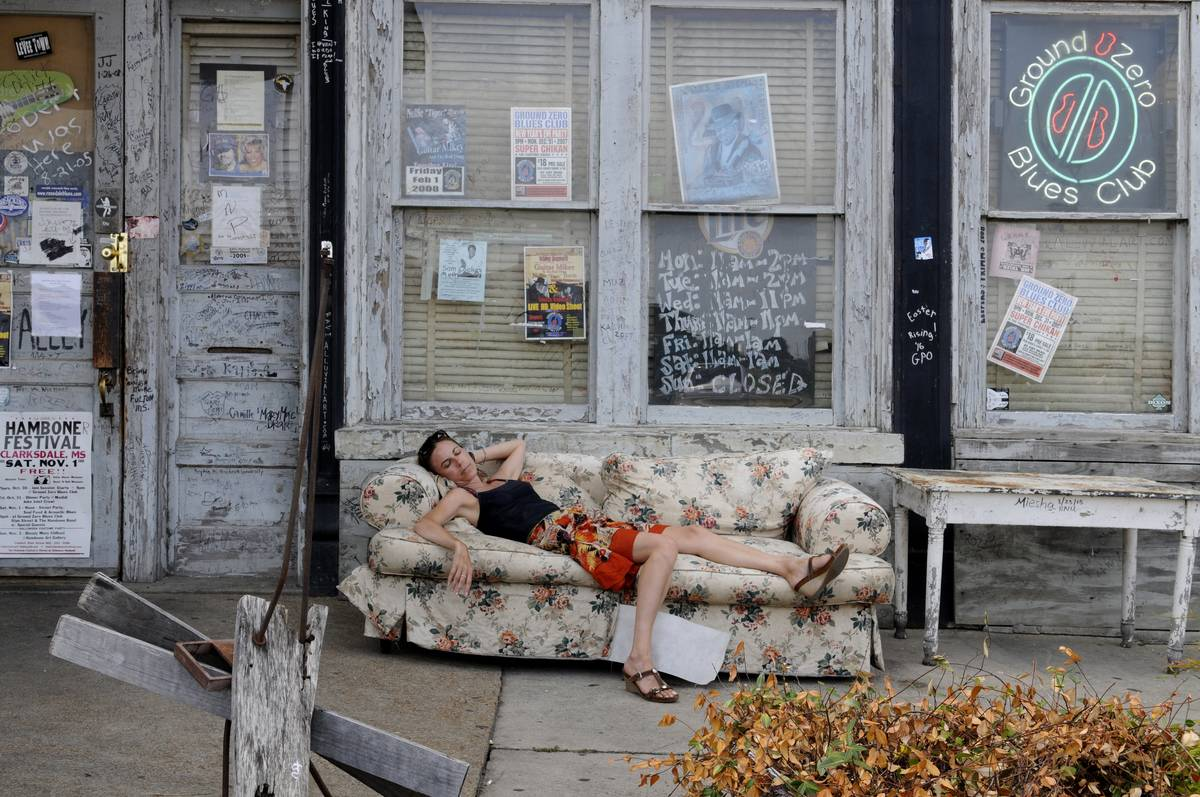 In a poor area of Mississippi, a woman sleeps on a couch outside.