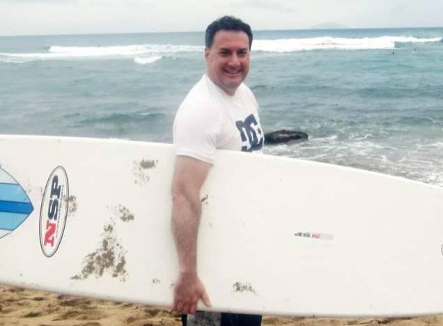 Joe Cartellone holds a surfboard at a beach.