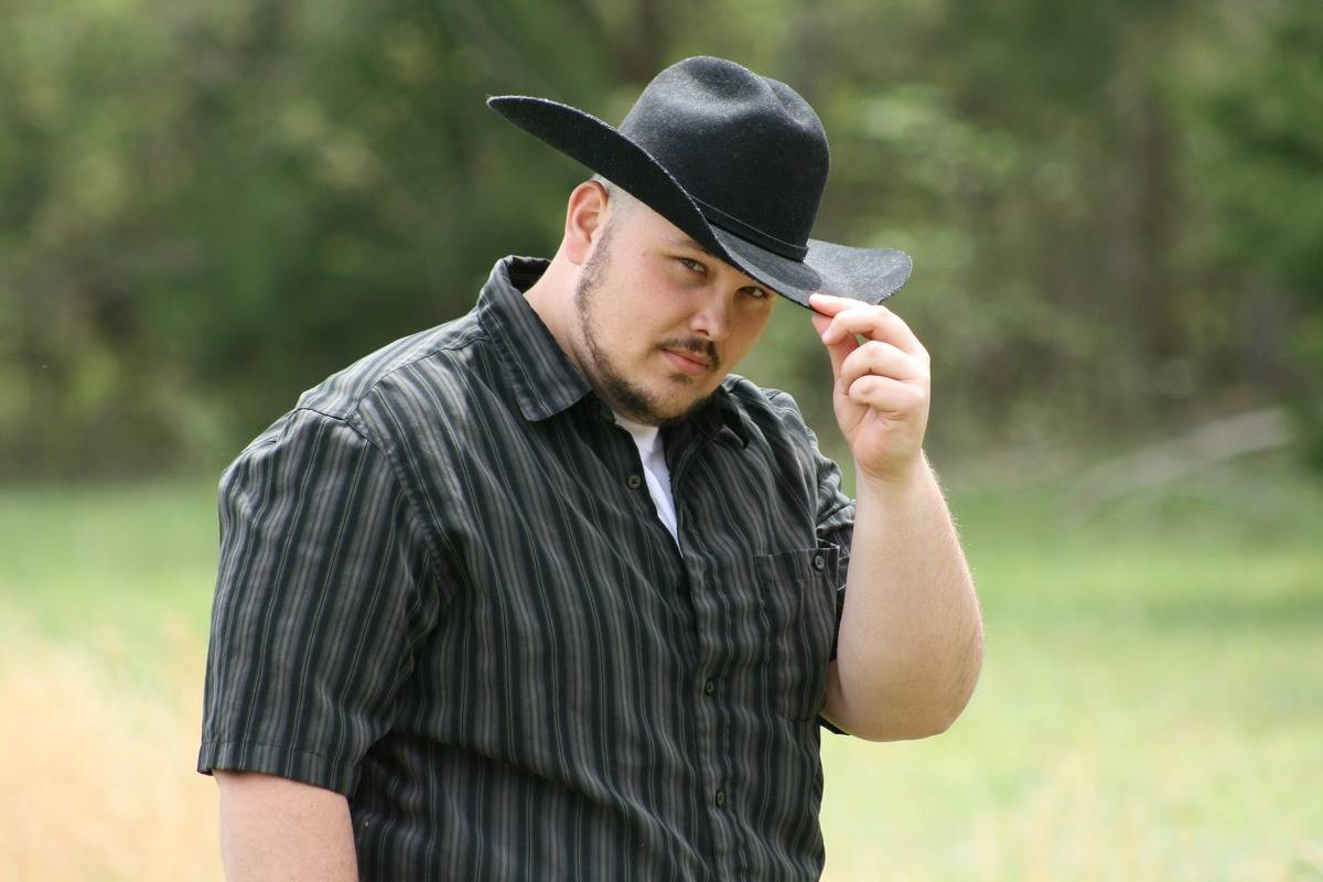 A man tips his cowboy hat in greeting.