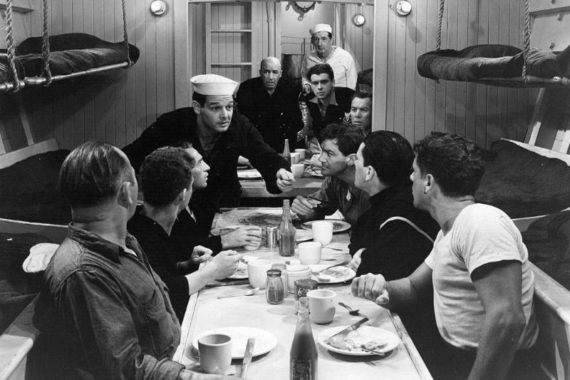black and white photo of soldiers eating on a submarine