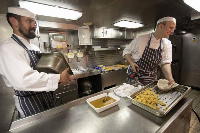 chefs preparing food on a submarine kitchen