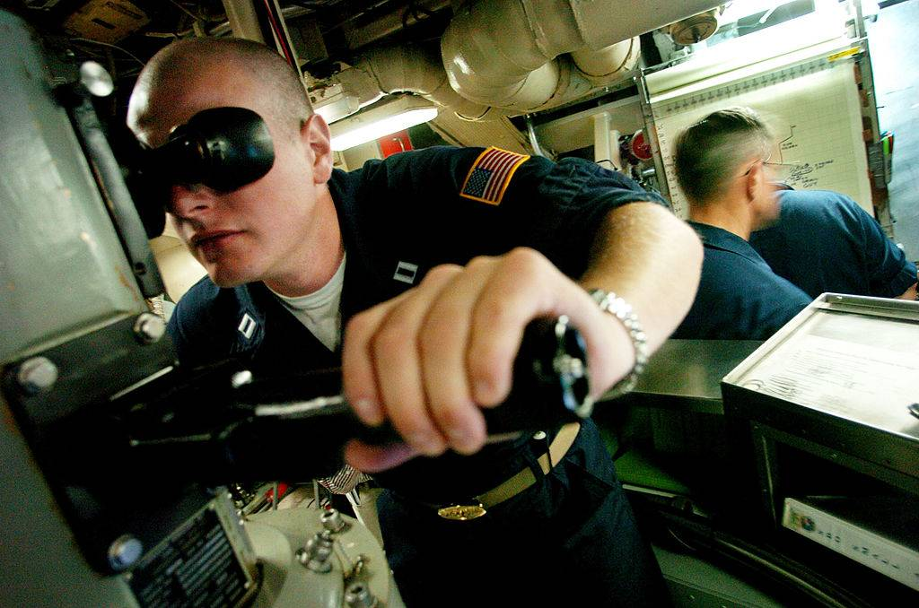 soldier looking through a parascope on a submarine