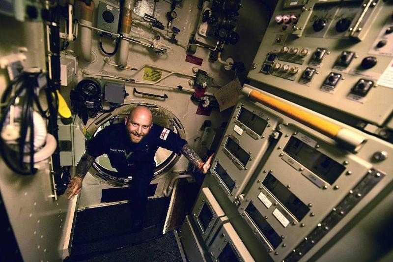 a crew worker walking through a submarine
