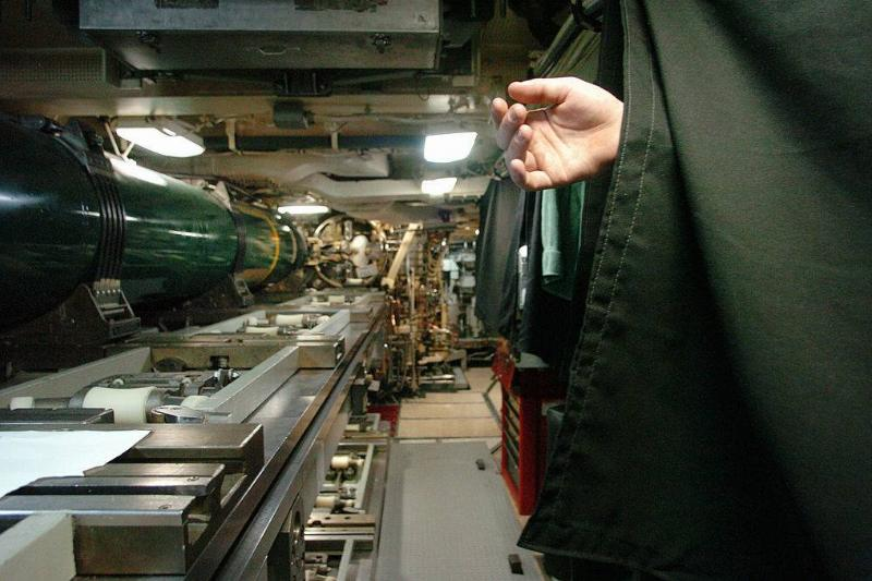 A sleeping sailor's hand hangs from a bunk bed in the missile room