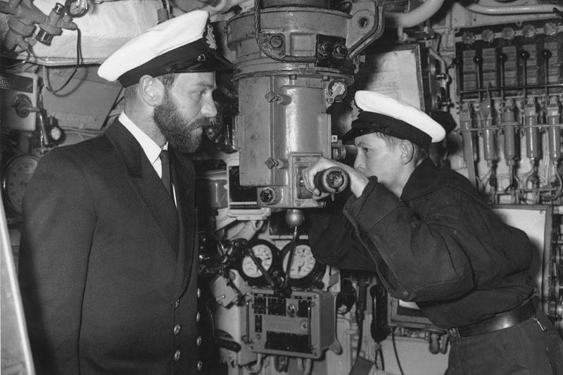 A sea cadet peers through the periscope of the submarine